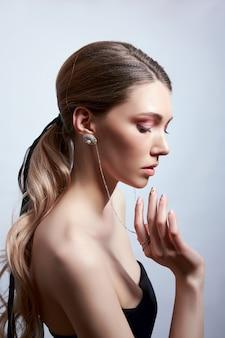 그녀의 귀에 긴 머리와 귀걸이와 여자의 아름다움 초상화