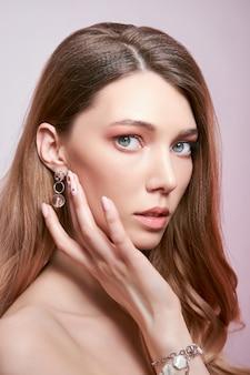 긴 머리를 가진 여자, 그녀의 귀에 귀걸이와 그녀의 손에 비싼 보석의 아름다움 초상