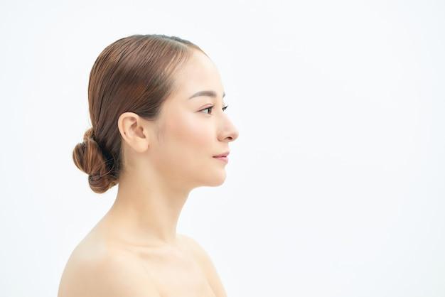 白い背景の上に孤立した目をそらしている完璧な肌を持つ若い魅力的な半裸の女性の美しさの肖像画