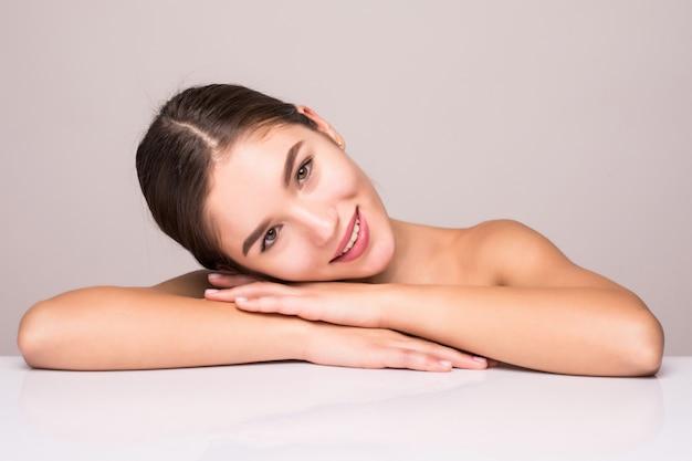 Портрет красотки молодой привлекательной полуголой женщины с совершенной кожей представляя и рассматривая белую стену