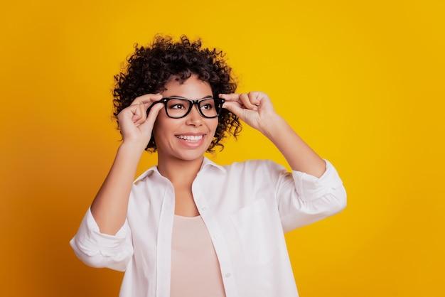 眼鏡をかけた若い黒人の健康な女性の美しさの肖像画は遠くに歯を見せる笑顔を見る