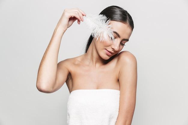 Портрет красоты молодой здоровой привлекательной брюнетки женщины, стоящей изолированно, держа перо
