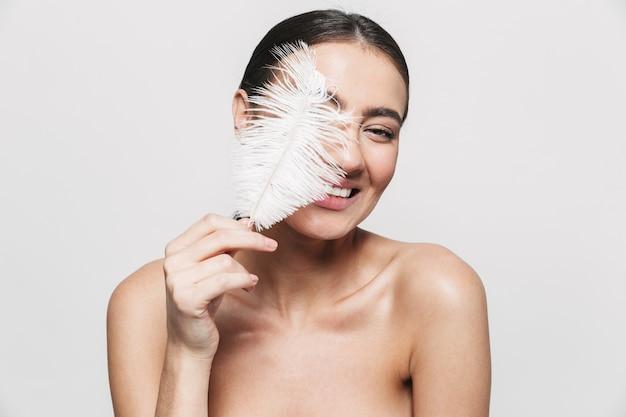 Портрет красоты молодой здоровой привлекательной брюнетки женщины, стоящей изолированно, держа перо Premium Фотографии