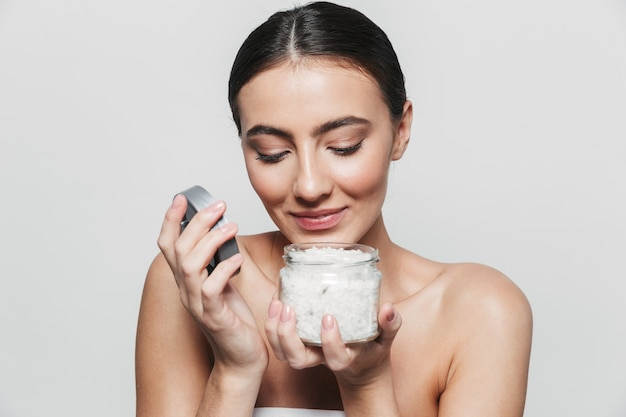 Портрет красоты молодой здоровой привлекательной брюнетки женщины, стоящей изолированно, держа банку спа-соли