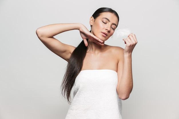 Портрет красоты молодой здоровой привлекательной брюнетки женщины, стоящей изолированно, позируя с пером