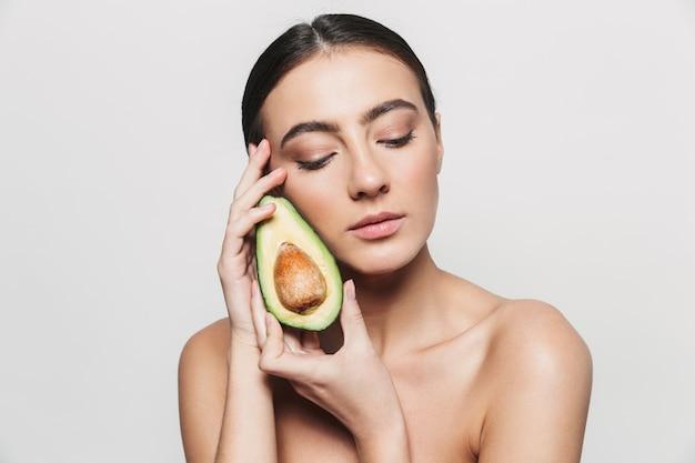 Портрет красоты молодой здоровой привлекательной брюнетки женщины, стоящей изолированно, позируя с нарезанным авокадо