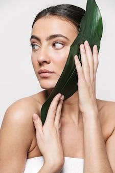 Портрет красоты молодой здоровой привлекательной брюнетки женщины, стоящей изолированно, позируя с зелеными тропическими листьями