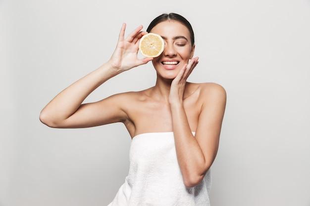 Портрет красоты молодой здоровой привлекательной брюнетки женщины, стоящей изолированно, позируя с нарезанным лимоном и апельсином