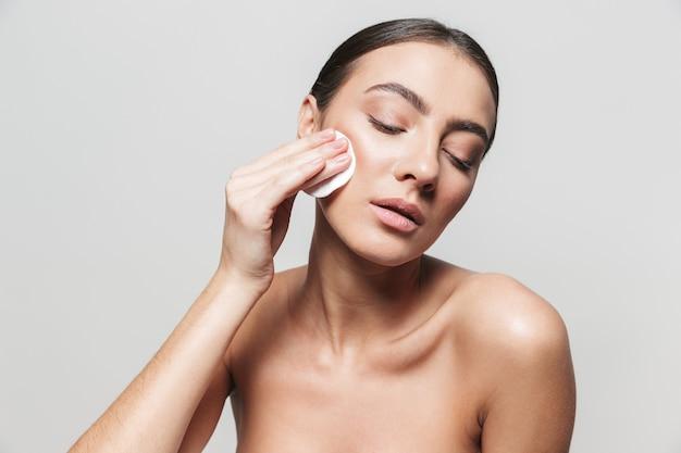 Портрет красоты молодой здоровой привлекательной брюнетки женщины, стоящей изолированно, используя ватный диск