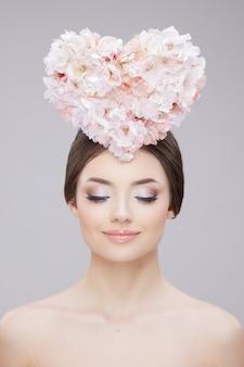 꽃으로 만든 큰 마음을 들고있는 젊은 여성의 아름다움 초상