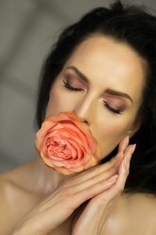 입에 장미와 함께 포즈를 취하는 닫힌된 눈을 가진 사랑스러운 갈색 머리 여자의 아름다움 초상화