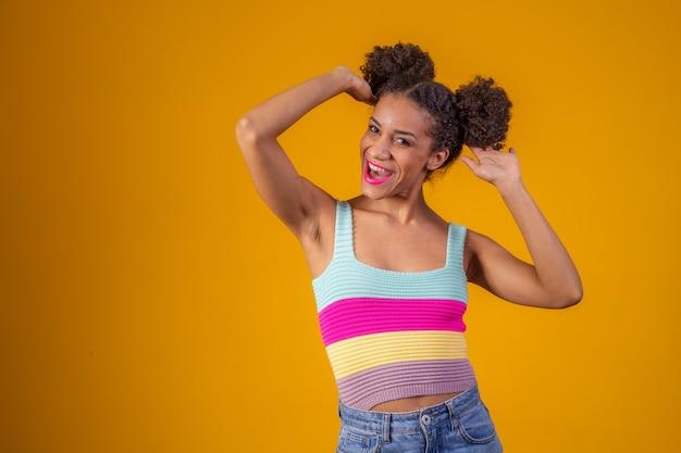 アフロの髪型と魅力的なメイクでアフリカ系アメリカ人の女性の美しさの肖像画。ブラジル人女性。混血。巻き毛。髪型。黄色の背景。カメラに微笑んでいるアフロの女性