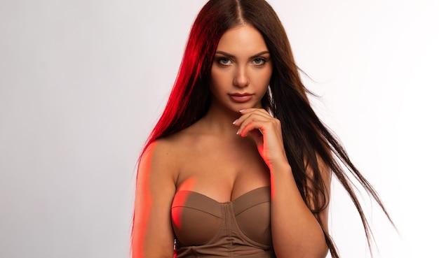 ベージュの壁にきれいな健康な肌を持つアメリカ人女性の美しさの肖像画。笑顔の美しい少女。巻き毛の黒い髪。