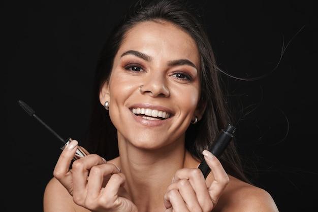 Портрет красоты привлекательной возбужденной молодой женщины топлес с длинными волосами брюнетки, изолированными над черной стеной, показывая тушь