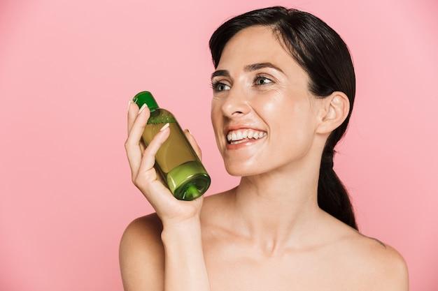 Портрет красоты привлекательной счастливой здоровой брюнетки топлес, изолированной над розовой стеной, показывая косметическую бутылку