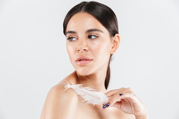 Портрет красоты привлекательной здоровой женщины, стоящей изолированной над белой стеной, позирующей с пером