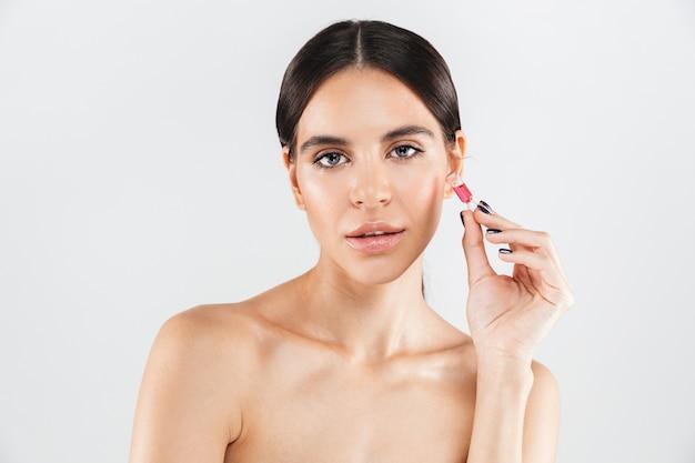 매력적인 건강 한 여자의 아름다움 초상화는 액체와 유리 캡슐을 보여주는 흰 벽 위에 절연 서