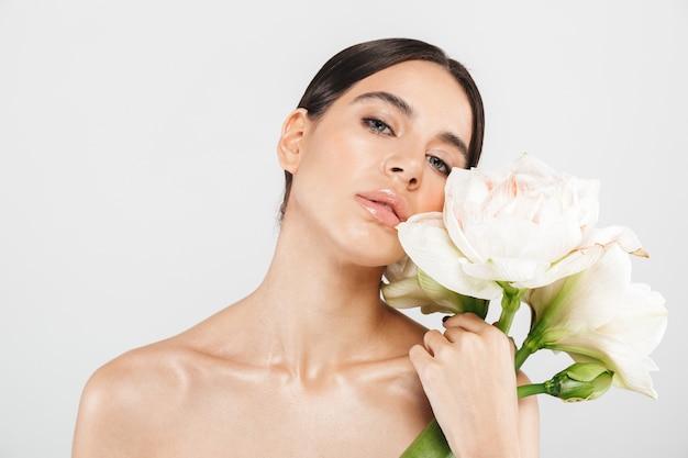 매력적인 관능적 인 건강 한 여자의 아름다움 초상화는 꽃과 함께 포즈, 흰 벽 위에 절연 서