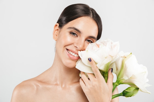 花でポーズをとって、白い壁の上に孤立して立っている魅力的な官能的な健康な女性の美しさの肖像画