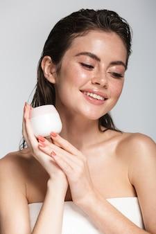 Портрет красоты привлекательной улыбающейся чувственной молодой женщины с мокрыми волосами брюнетки, стоящими изолированными на сером, показывая пустую банку для крема для лица