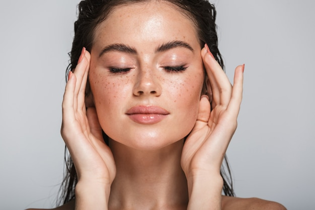 Портрет красоты привлекательной улыбающейся чувственной молодой женщины с длинными волосами мокрой брюнетки, стоящей изолированной на сером, касаясь ее лица, позирует