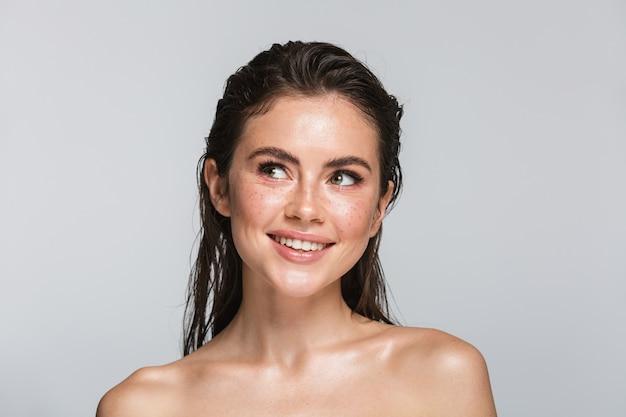 Портрет красоты привлекательной улыбающейся молодой топлес брюнетки, стоящей изолированной на белом