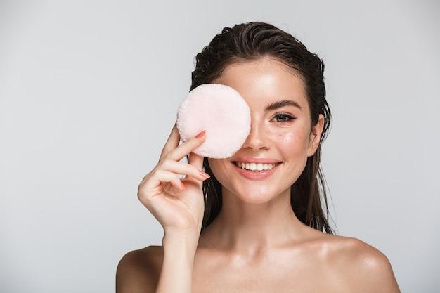 Портрет красоты привлекательной улыбающейся молодой топлес брюнетки, стоящей изолированной на белом, держа слойку пудры для макияжа