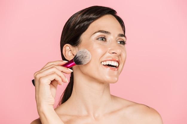 ピンクの壁に孤立して立っている、化粧ブラシを保持している魅力的な笑顔の若いトップレスの女性の美しさの肖像画