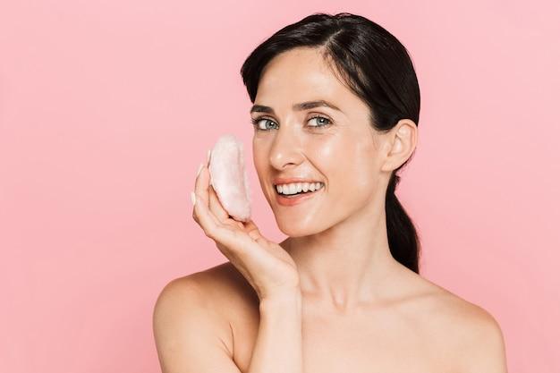 パウダーパフを使用して、ピンクの壁の上に孤立して立っている魅力的な笑顔の若いトップレスの女性の美しさの肖像画