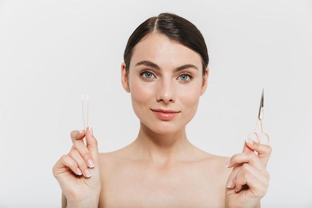 Портрет красоты привлекательной молодой женщины брюнетки, стоящей изолированно над белой стеной, выщипывая волосы пинцетом, показывая ножницы