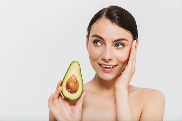 Портрет красоты привлекательной молодой женщины брюнетки, стоящей изолированной над белой стеной, показывая нарезанный авокадо
