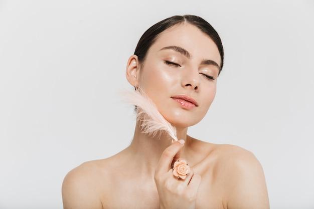 Красота портрет привлекательной молодой брюнетки женщины, стоящей изолированной над белой стеной, касаясь лица с пером