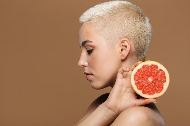 ベージュの壁に分離されたグレープフルーツを保持している魅力的な若いトップレス金髪の短い髪の女性の美しさの肖像画