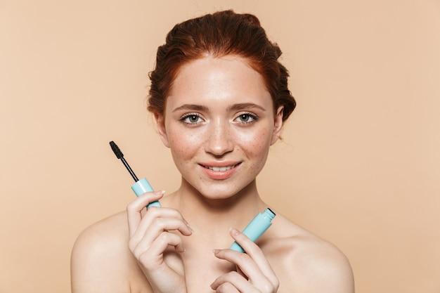 マスカラを適用して、孤立して立っている魅力的な若いトップレス赤毛の女性の美しさの肖像画