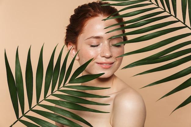 熱帯の葉に囲まれてポーズをとって、孤立して立っている魅力的な若いトップレス赤毛の女性の美しさの肖像画