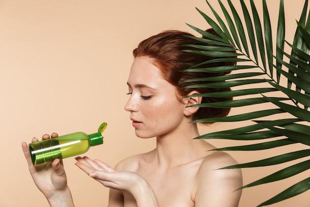 孤立して立っている魅力的な若いトップレス赤毛の女性の美しさの肖像画、化粧ローションボトルを示して、熱帯の葉に囲まれてポーズをとる