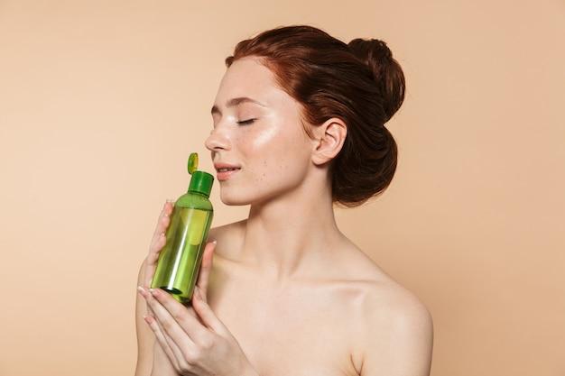 化粧ローションボトルを見せて、孤立して立っている魅力的な若いトップレス赤毛の女性の美しさの肖像画