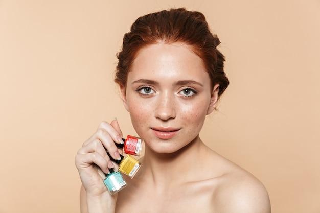 Красота портрет привлекательной молодой топлес рыжей женщины, стоящей изолированно, показывая лак для ногтей