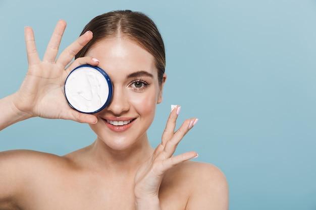 Портрет красоты привлекательной молодой женщины топлес, изолированной над синей стеной, наносящей крем из контейнера