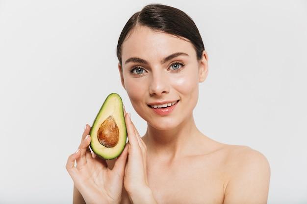 Портрет красоты привлекательной молодой женщины топлес, изолированной над белой стеной, показывая нарезанный авокадо