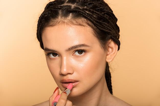 ピンクの口紅を適用して、ベージュの壁の上に孤立して立っている魅力的な若いトップレスの女性の美しさの肖像画