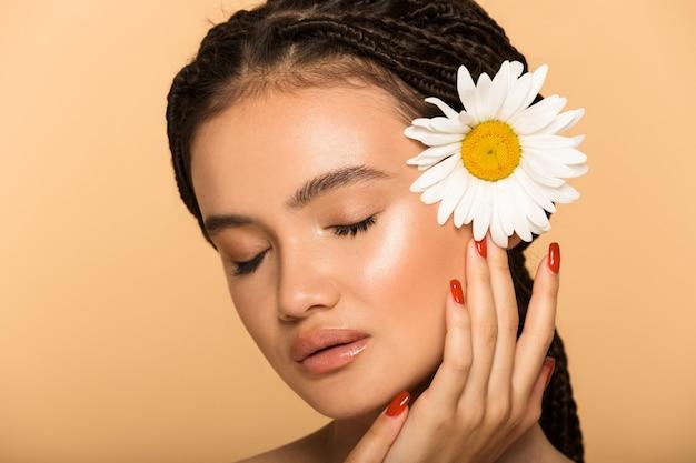 ベージュの壁に孤立して立っている魅力的な若いトップレスの女性の美しさの肖像画、カモミールの花でポーズ、目を閉じて