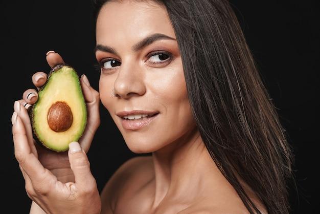 Портрет красоты привлекательной молодой женщины топлес с длинными волосами брюнетки, изолированной над черной стеной, позирующей с нарезанным авокадо