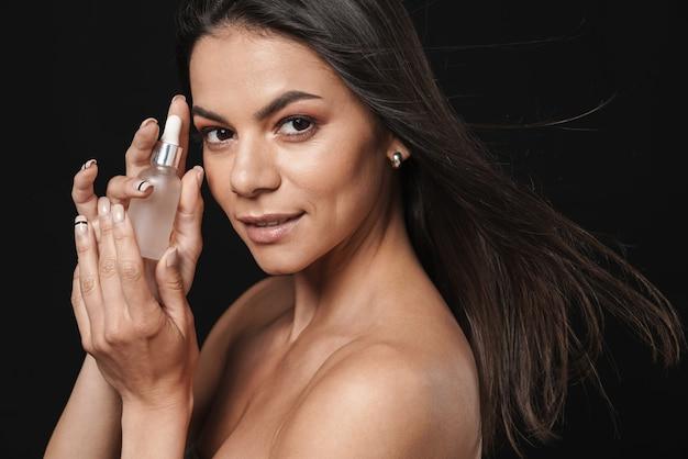 Портрет красоты привлекательной молодой женщины топлес с длинными волосами брюнетки, изолированными над черной стеной, показывая масло красоты макияжа
