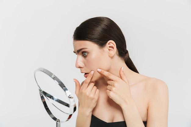 흰 벽에 격리된 매력적인 젊은 여성의 미인 초상화, 거울을 보고, 얼굴을 검사