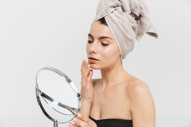 Портрет красоты привлекательной молодой женщины, изолированной над белой стеной, смотрящей в зеркало, исследующей лицо