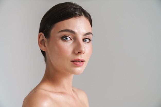 Портрет красоты молодой топлес брюнетки, стоящей изолированной на сером