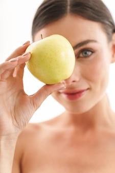 青リンゴを示す、白で隔離されて立っている若いトップレスブルネットの女性の美しさの肖像画