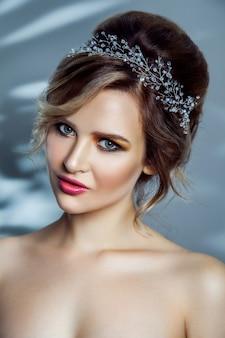 메이크업과 수집된 헤어스타일을 한 아름다운 패션 모델의 아름다움 초상화. 파란색 배경에 촬영 스튜디오입니다.