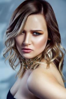 그녀의 목에 메이크업, 컬러 웨이브 헤어스타일 및 액세서리와 함께 아름 다운 패션 모델의 아름다움 초상화. 파란색 배경에 촬영 스튜디오입니다. .